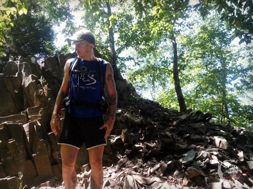 Geoffrey Hart standing on a rock covered trail during the 7 Sisters trail race, Holyoke MA