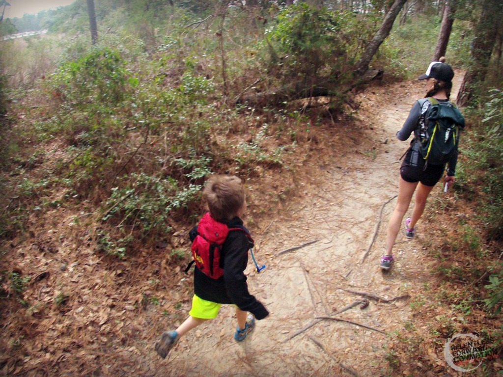 Mom and son trail running through the forest