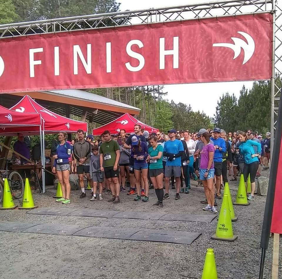 Starting line of a small 5K trail race showing runners waiting for the starting gun to go off