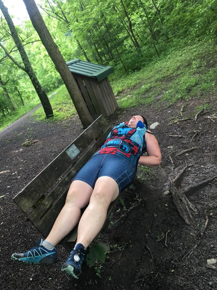 sleep during a 100 mile race.   Ultrarunner taking a nap on a wooden bench in the forest in the middle of an ultramarathon.