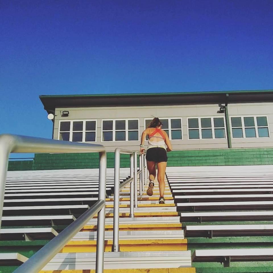 Heather Hart running up stadium stairs as a part of 100K ultramarathon training