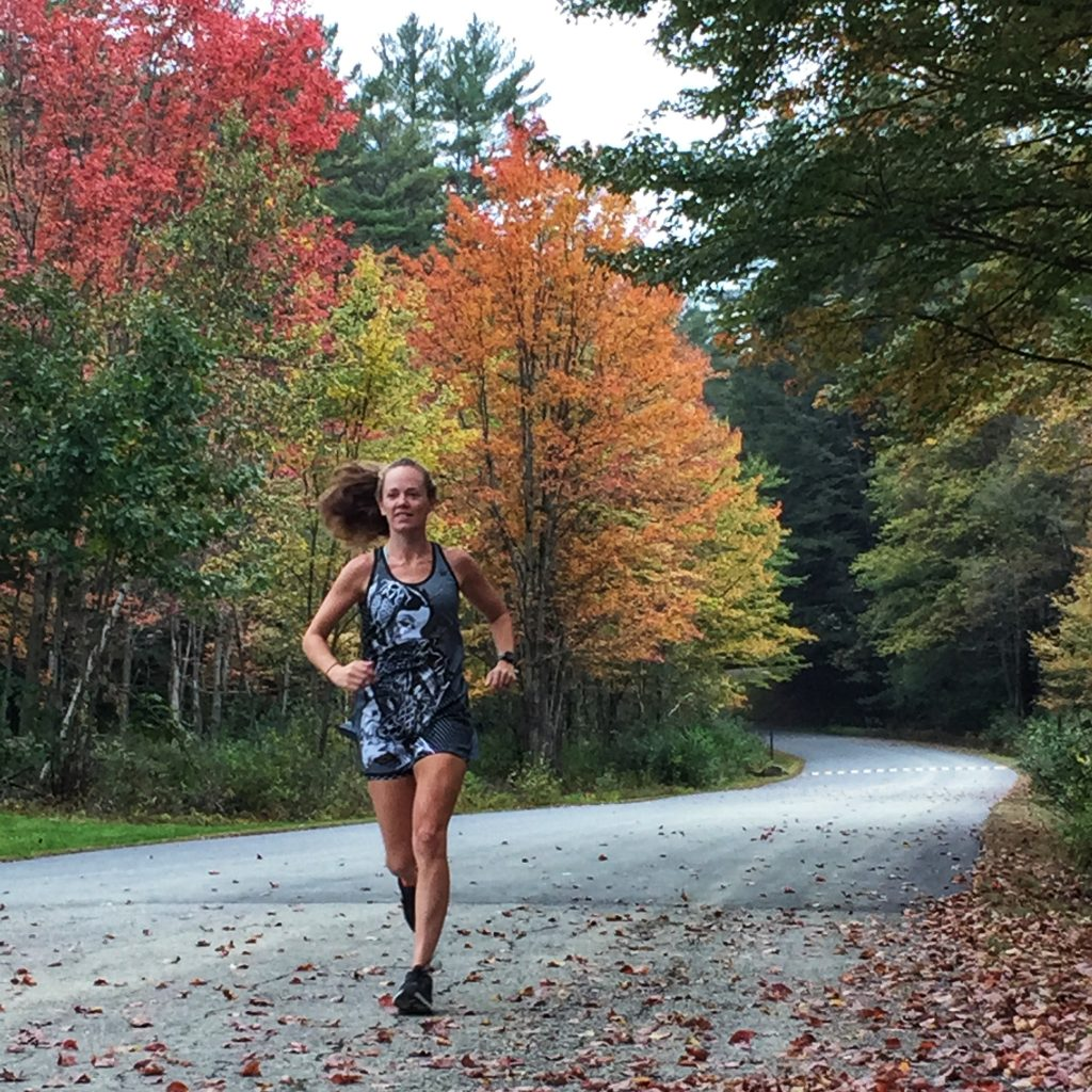 Woman running through brightly colored fall leaves
