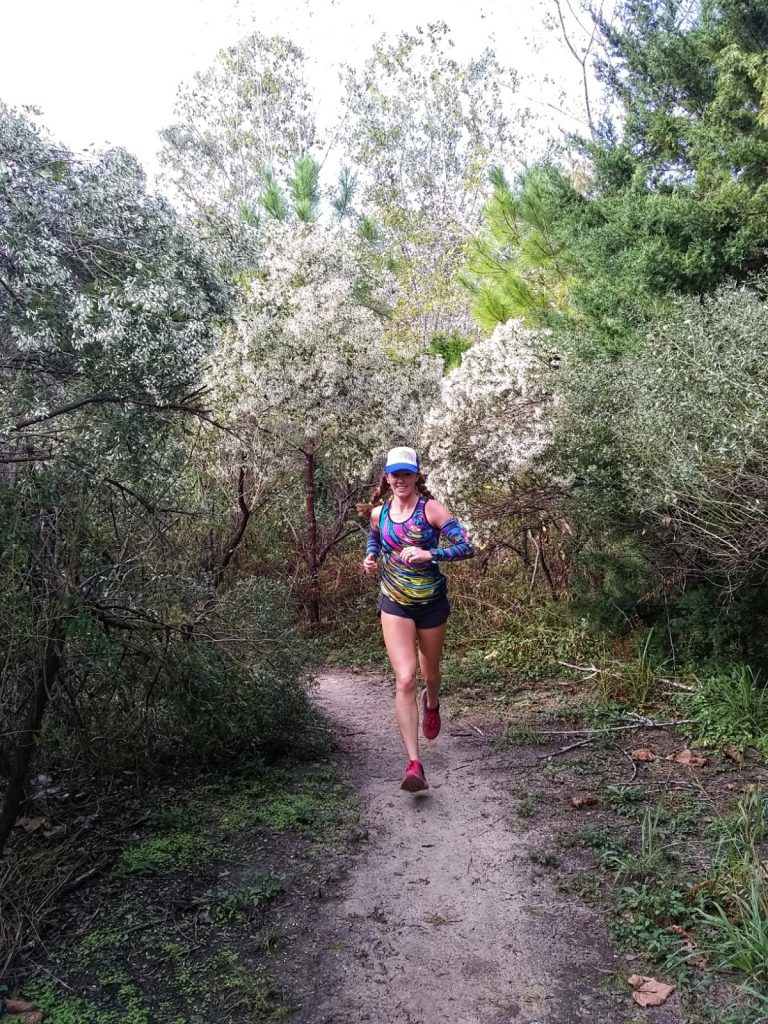 Heather Hart running down a trail surrounded by blooming trees