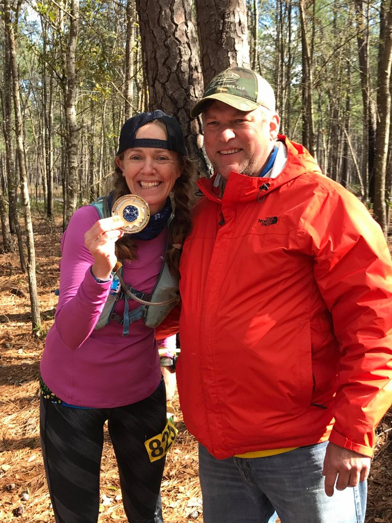 Heather Hart holding a 100 mile ultramarathon buckle