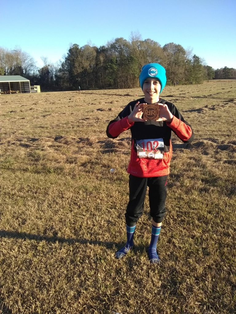 Pre-teen proudly holding up his finishers trophy at the end of a running event