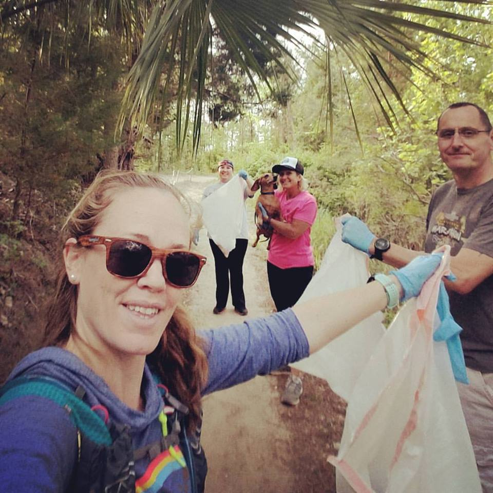 Environmentally responsible trail runners cleaning up their local trail holding garbage bags