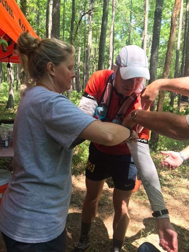 Preparing your crew for an ultramarathon.  Crew member puts ice in runner's arm sleeves.