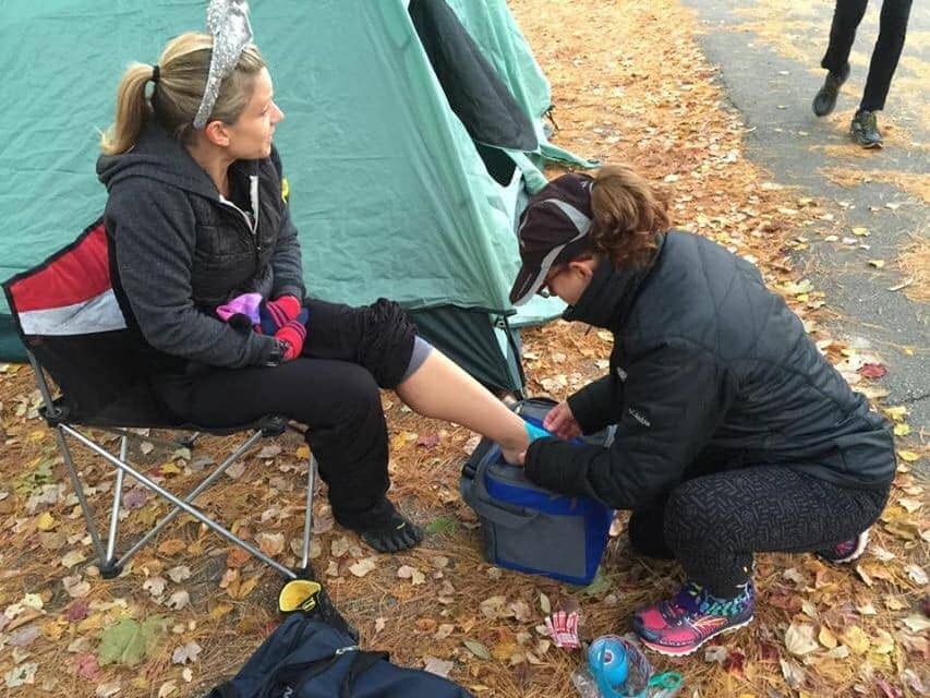 Crew member tapes runners foot during ultramarathon