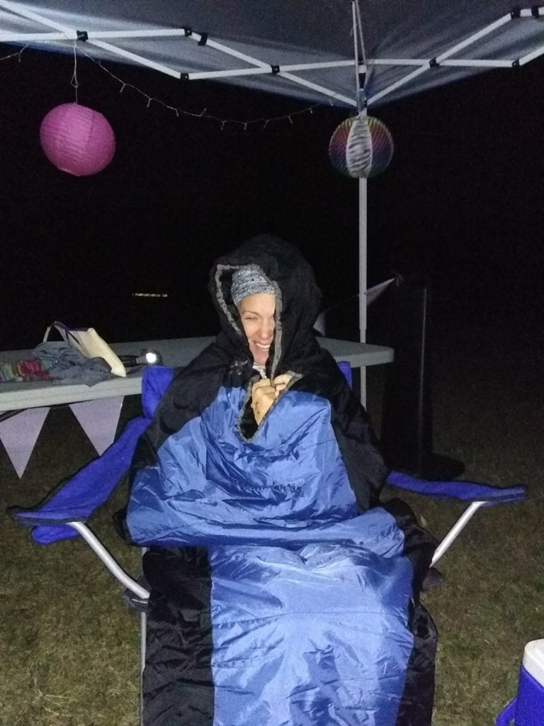 Woman huddled in sleeping bag while sitting in a chair