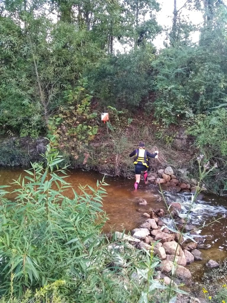 Adventure racer crossing a small stream to reach a check point during a race