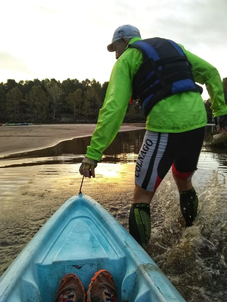 Adventure racer pulling a kayak into the water during a race