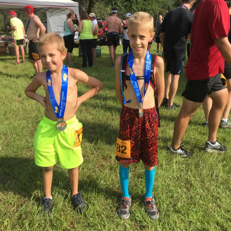 two young kids wearing finishers medals at the end of a 5K