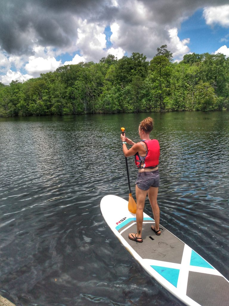 Paddle boarding while wearing Earth Runner's Cadence Adventure Sandals
