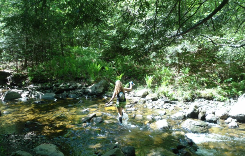 Heather Hart crossing a stream during 2015 Infinitus Ultramarathon