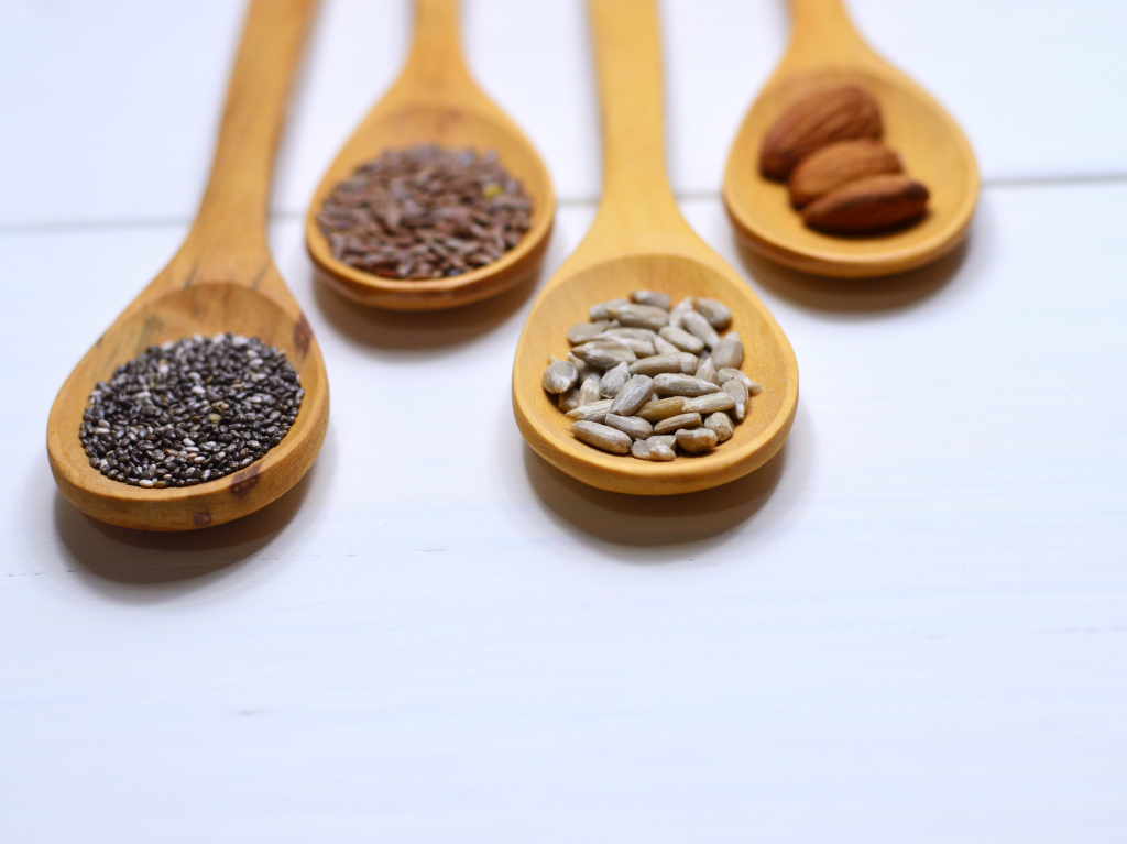 Seeds, full of omega fatty acids, on wooden spoons.  Ideal to add into your ultramarathon diet.