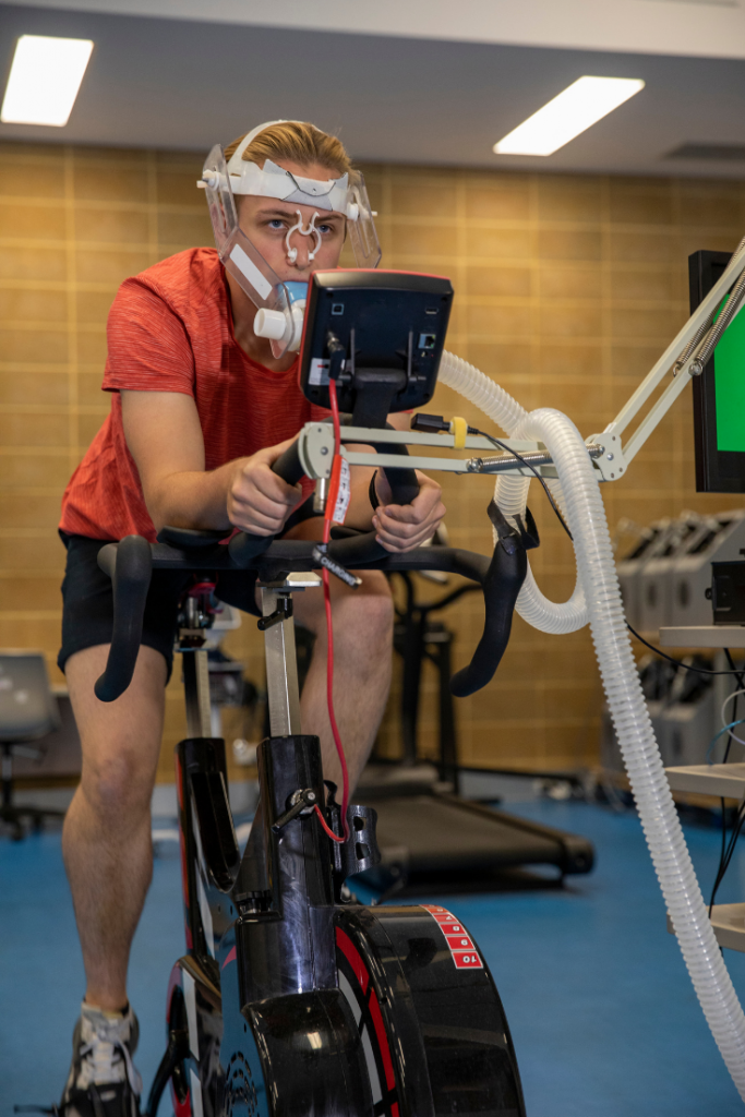 Athlete performing a VO2max test on a bicycle in an exercise science lab