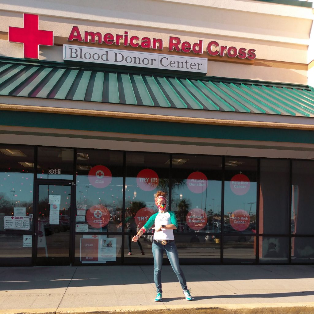 A runner donating blood standing in front of the American Red Cross after donation