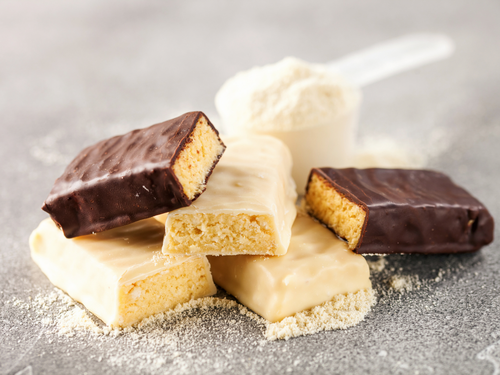 A photo of protein bars and protein powder.  Focusing only on protein and not replenishing with glycogen is one of the top nutrition mistakes runners make.