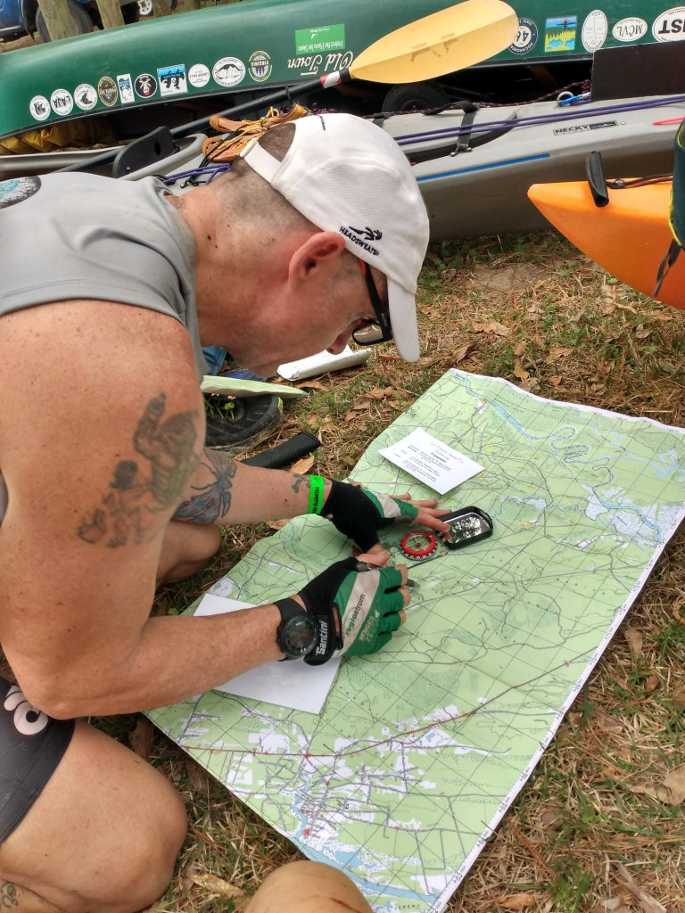 Adventure Racer bent over a map focused on triangulating check points using a compass.