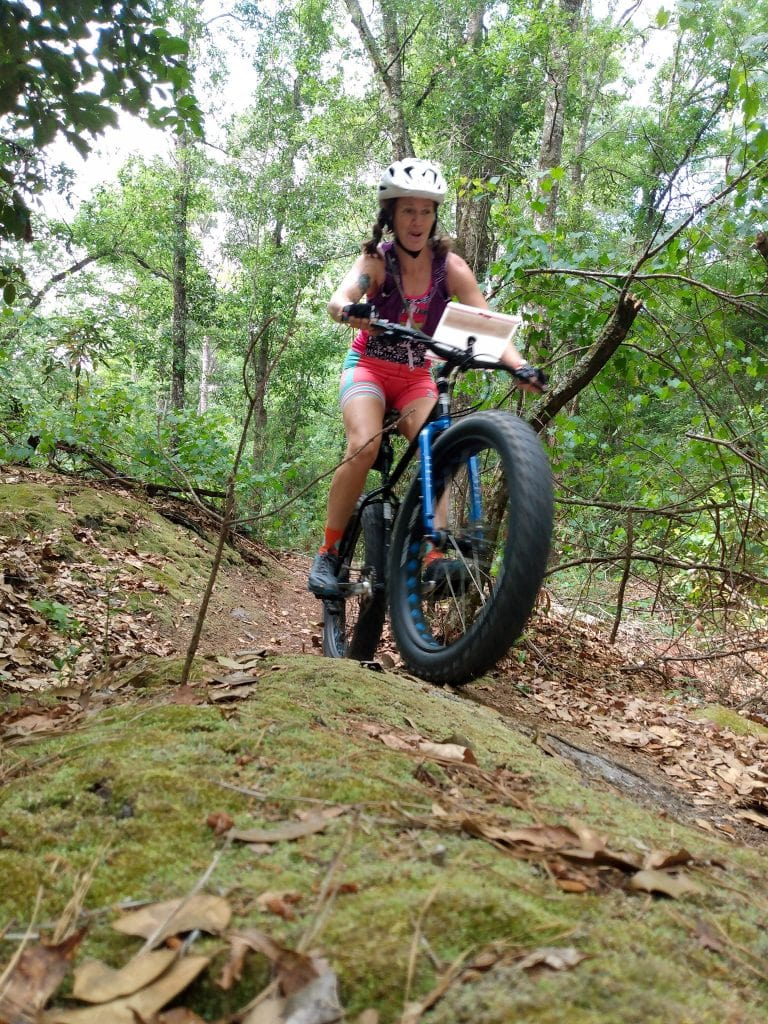 Heather Hard riding mountain bike through the forest trails