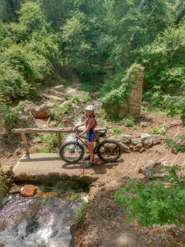 Woman riding mountain bike on bridge near forest