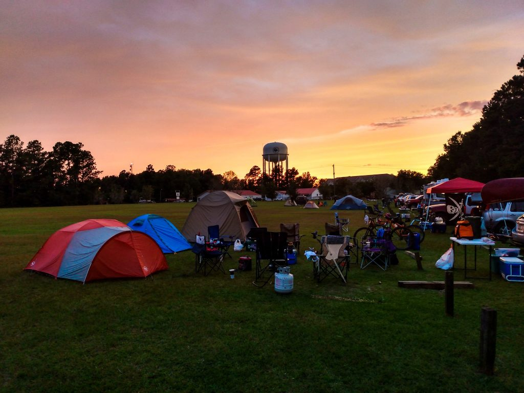 Group of tents and people camping before a trail race with the sun setting in the background