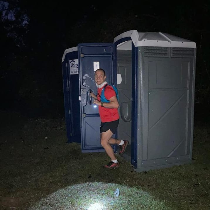 Male runner walking out of a port-a-potty before a trail race