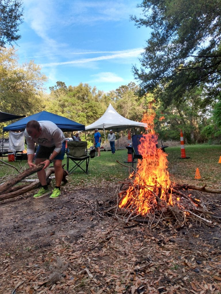 man builds campfire at a trail race