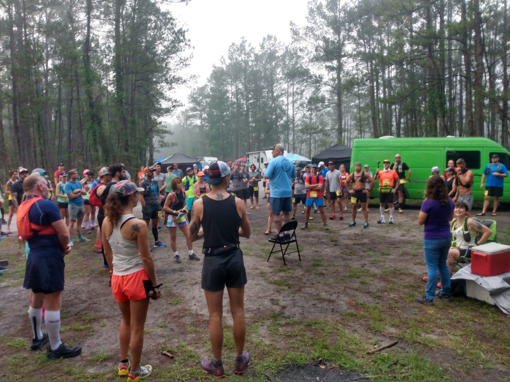Race director giving instructions to a group of trail runners before a race