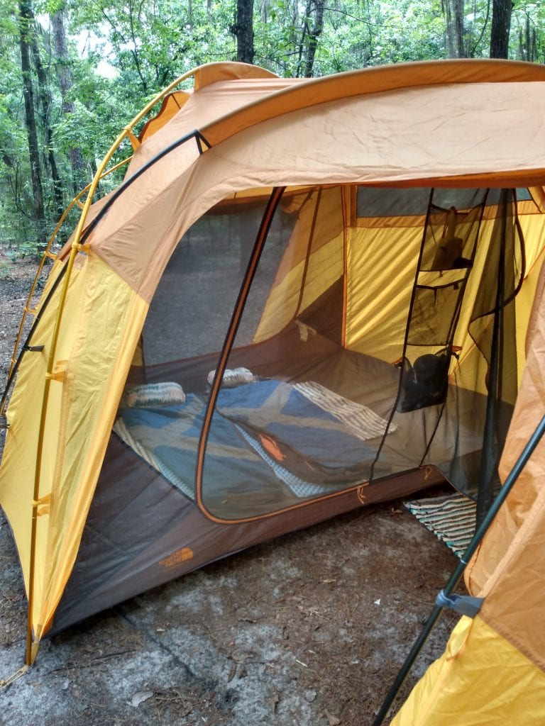 View inside of a tent with sleeping bags laid out on the floor.