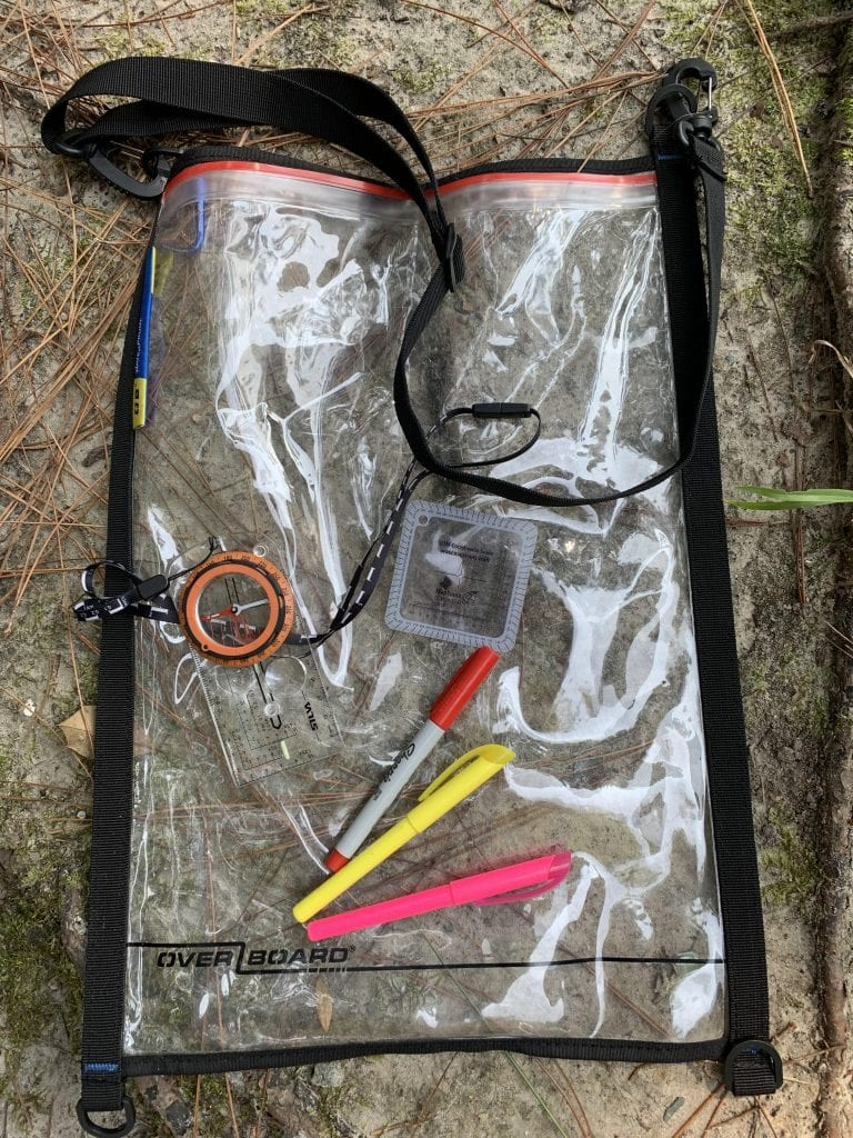 Adventure Race Gear including a wateproof map case, compass, UTM plotting tool, markers, and highlighters.